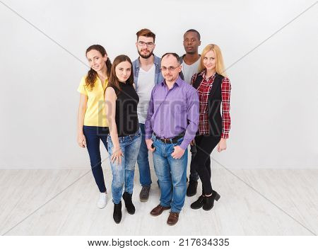 Multiethnic group of adults standing on white background, copy space