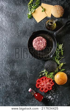 Ingredients for cooking hamburger. Meat beef burger in pan, cheese, ketchup sauce, tomato, black and white buns, arugula salad over dark texture background. Top view with space. Homemade fast food