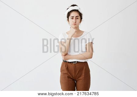 Portrait of young annoyed female with dark wavy hair in bun and pursed lips having dissatisfied look, frowning face. Stubborn teenage girl has her own style looks angry, irritated, keeps hand under chin. Studio shot, horizontal