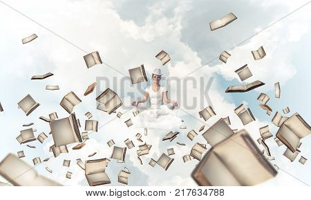 Woman in white clothing keeping eyes closed and looking concentrated while meditating among flying books in the air with cloudy skyscape on background.