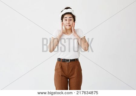 Shocked surprised female model with dark hair in bun being scared by someone, looks horrified, recieves bad news, bits her lip, with popped dark eyes. Young woman in stupor realizes bad failure or mistake