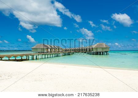 Wooden villas over water of the Indian Ocean Maldives. Sandy beach and turquoise ocean water.