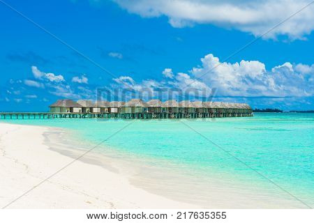 Dhidhoofinolhu Maldives - 27 July 2017: Wooden villas over water of the Indian Ocean Maldives. Sandy beach and turquoise ocean water.