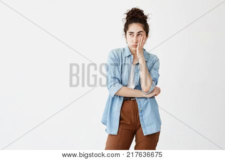 Isolated portrait of stylish young woman with dark hair in bun in denim shirt touching her chin and looking sideways with doubtful and sceptical expression, making important life decision.