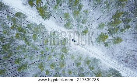 View from height on car driving through winter forest road. Scenic winter landscape