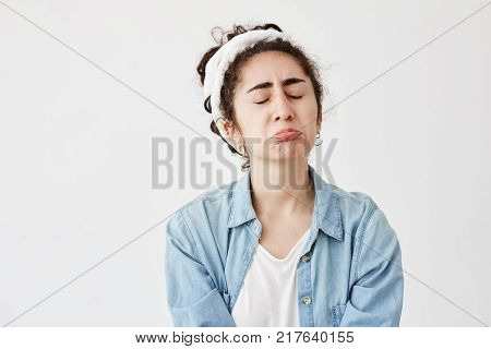Miserable upset sad gloomy female with dark and wavy hair looks offended, pouts lips, frowns face in dispair, frustrated, after receiving bad news. Unhappy young girl in denim shirt cries in frustration