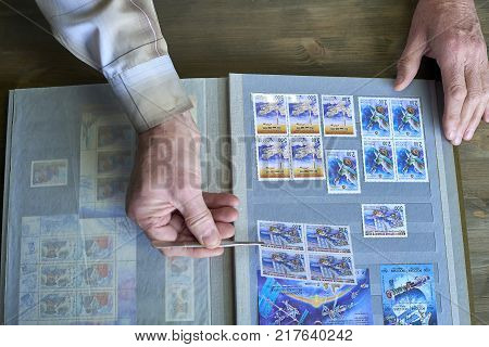 Senior man hands hold tweezers and stamp album with postage stamps collection, space theme, wooden background