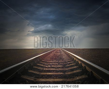 rails going away to the dark rainy clouds. gloomy landscape. Black and white image with rails going away into the dark sky landscape