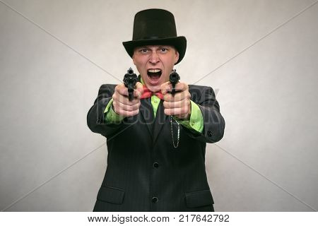 The spy. Secret service. Angry Detecive agent holds pistol gun in his hands aiming and attack. Retro wicked gangster isolated on white background.