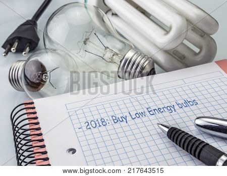 Calculator and money next to a light bulb, writing in agenda year 2018 to buy bulbs of low consumption, the concept of energy saving