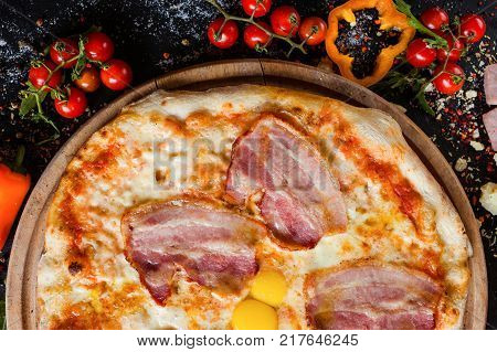 Carbonara pizza with bacon and eggs. Simple nourishing traditional recipe