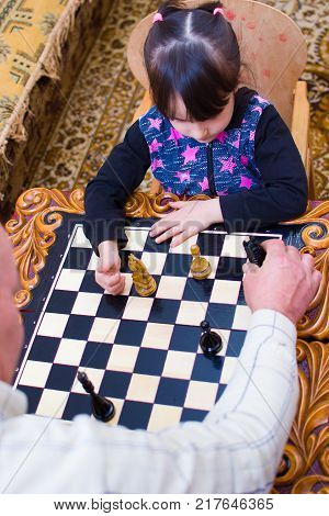 Granddaughter Plays Chess With His Grandfather. Grandfather Teaches To Play
