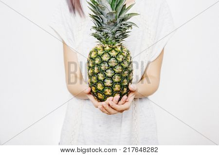 girl holds pineapple. Young woman with pineapple. fruits and vegetables in their hands. pineapple on the head.