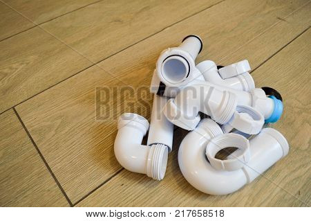 White plastic plumbing plumbing pipes smooth and curved fittings flanges rubber gaskets. Against the background of beige boards.