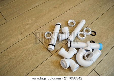 White plastic plumbing plumbing pipes smooth and curved fittings flanges rubber gaskets. Against the background of beige boards. Place for the inscription.