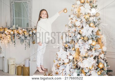 Small adorable female child in white sweater and trousers holds toy for decoration decorates New Year tree. Cheerful little kid near Christmas tree. New Year`s Eve. Holidays and people concept