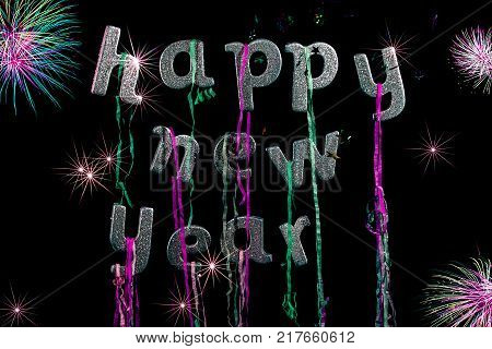 Happy new year party. Sliver glitter text with fireworks. Greeting card image. Sparkly words with party popper streamers stars and dazzling fireworks. Black background.