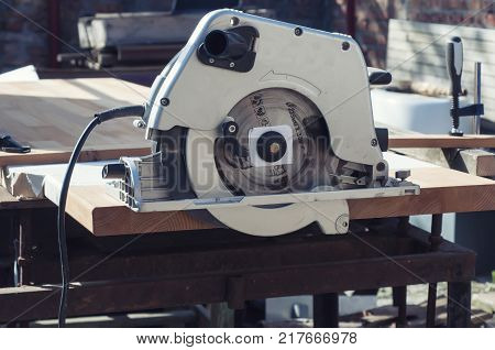 Close up electric saw to sawing wood board, solf focus.