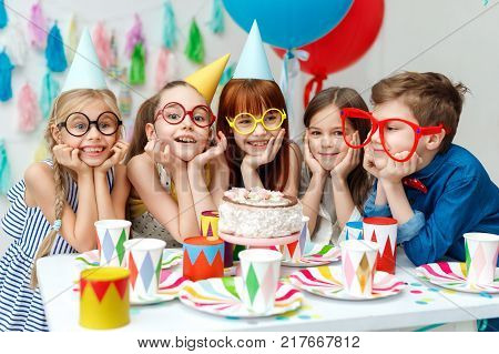 Portrait of funny group of children wear party caps, big spectacles, look with big appetite on birthday cake, want to taste it, have special occasion, spend time happily. Celebration, holidays concept