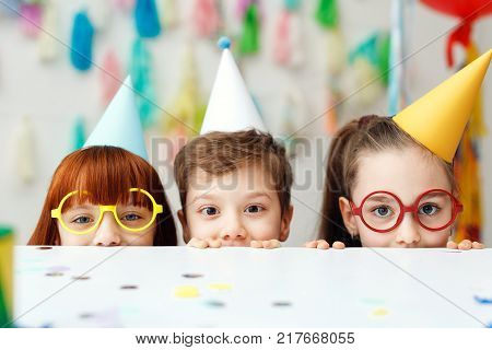 Two adorable girls in eyewear and one boy play game together, celebrate festive event, hide behind table, have cheerful funny expressions, look directly into camera. Childhood and celebration