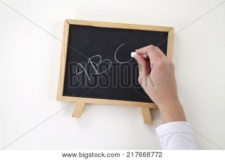 young woman writing ABC on a blackboard