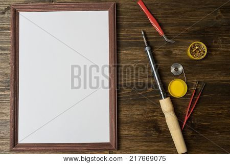 soldering iron with soldering accessories on wooden background.