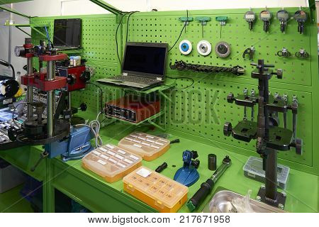 View on green working place with equipment and tools for car trucks components parts details diagnostic calibration maintenance repair works. Car diagnostic station. Car maintenance MOT equipment
