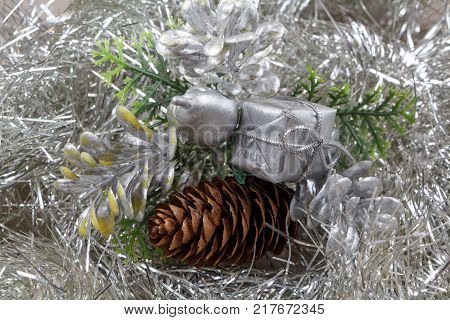 Gift and pine cones on a silvery tinsel as decoration for Christmas