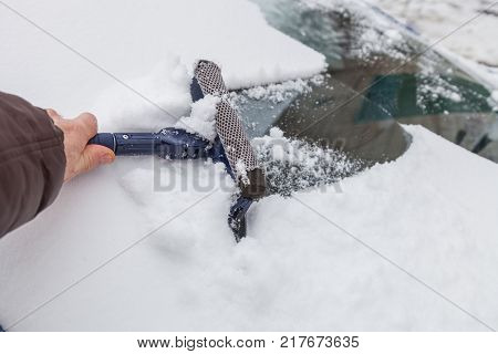 Cleaning the windshield of the car from snow and ice with scraper in winter