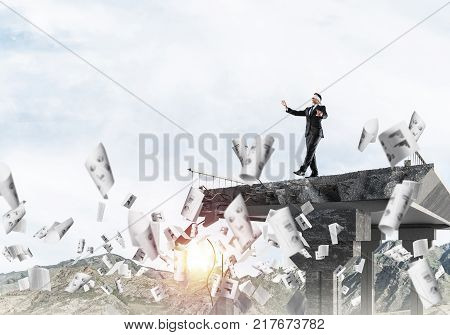 Businessman walking blindfolded among flying documents on concrete bridge with huge gap as symbol of hidden threats and risks. Skyscape and nature view on background. 3D rendering. poster