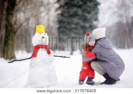 Little boy with his mother/babysitter/grandmother building snowman in snowy park. Active outdoors leisure with children in winter. Kid embrace with his mother