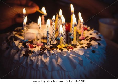 anniversary cake with hand burning candles in dark. A hand with a match lights the candles on the birthday cake with white cream. 16 sixteen candles on the cake.
