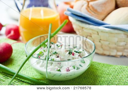 Quark with fresh radish and chive in a glass bowl