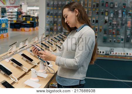 Smart female customer choosing smartphone in the mobile phone shop. difficult decision. Various choice. She is holding smartphone