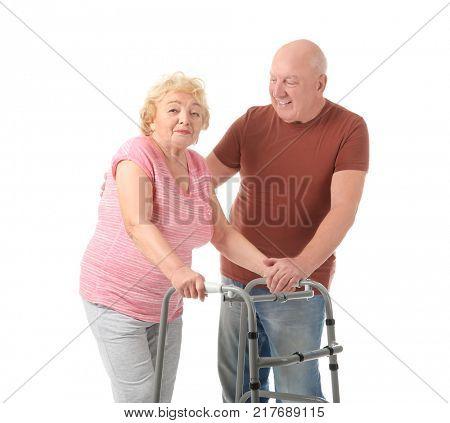 Elderly couple with walking frame on white background