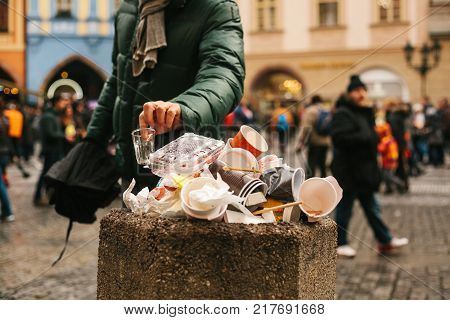 Unknown man throws trash into basket. Hand of an unknown man throws disposable cup into overcrowded trash basket on the street of Prague against blurred crowd of people
