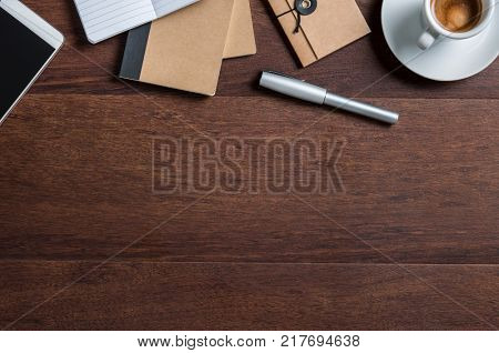 Top view of business office desk with cup of coffee, smartphone, diary and pen. High angle view of office wooden table with copy space. Flat view of professional desk with office supplies.