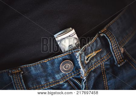 Macro shot of trendy jeans with american 100 dollar bill on its pocket. Bill with Benjamin Franklin folded and stuffed into the pants and panties of a prostitute.