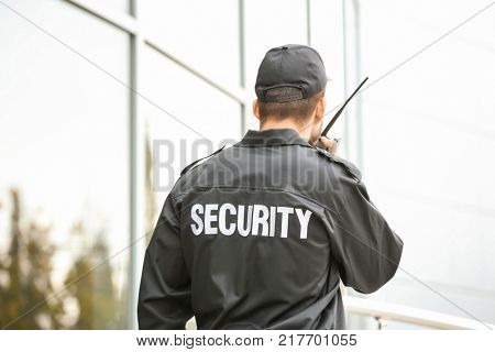 Male security guard using portable radio transmitter near building outdoors