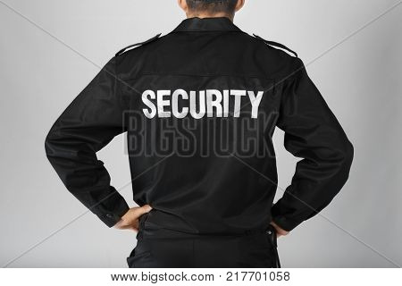 Male security guard on light background, closeup