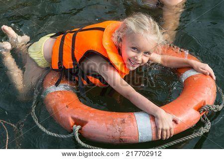 Happy girl with lifebuoy and life jacket enjoying in sea.