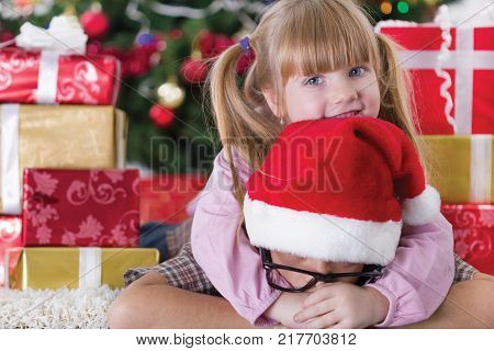 The younger sister embrace boy on Christmas evening