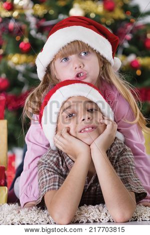 happy boy laughing in his sister embrace on Christmas evening