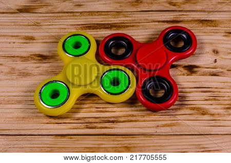 Two Fidget Spinners On Wooden Desk