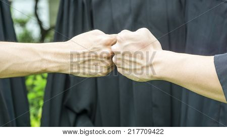 people with black gowns hand fist clash