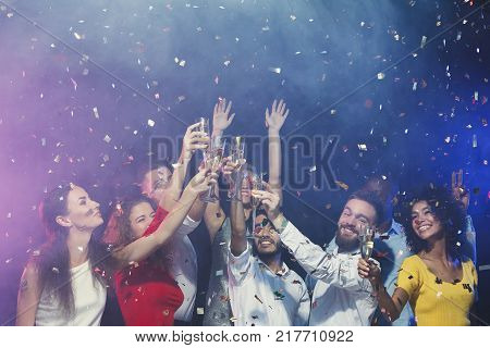 Christmas party time. Young people toasting with champagne flutes. Multiethnic friends congratulating each other with new year. Holidays, celebration and nightlife concept