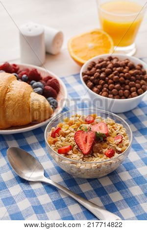 Rich continental breakfast menu. French crusty croissants, muesli, glass of orange fresh , yogurt and boiled eggs for tasty morning meals on checkered tablecloth