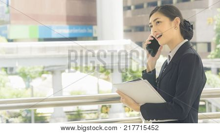 Asian business woman uses and talks on mobile phone with paper work on her hand at outdoor