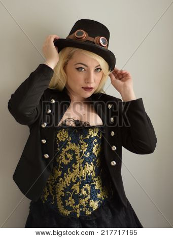 Young Steampunk girl holds hat with goggles and elaborate corset looking directly at viewer