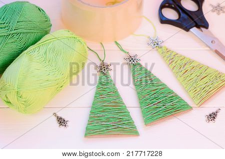 Original Christmas trees decor on a wooden table. Easy and cheap idea for recycled crafts and Christmas home decorating with old cardboard box and green cotton yarn